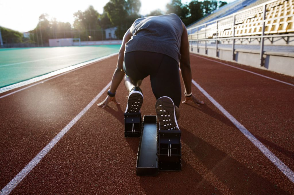 Back view of a young male athlete at starting block